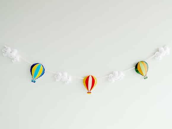 Fios de costura, papéis coloridos, tesoura, cola e muita imaginação. Vale colocar algumas nuvens e corações. Exemplo da Arcobaleno Studio